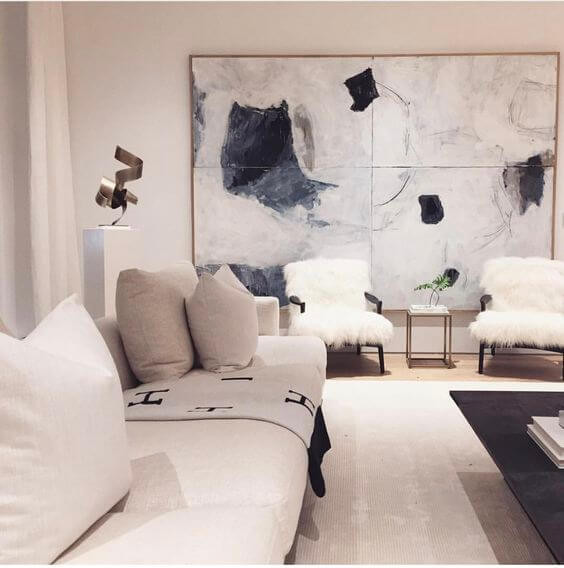 A beige and cream coloured lounge room. The floor is cream carpet; a beige fabric lounge sits on the left. A black glass coffee table is on the right with shaggy cream single chairs at the back of the room. A large abstract artwork in white and dark blue hangs on the back wall.