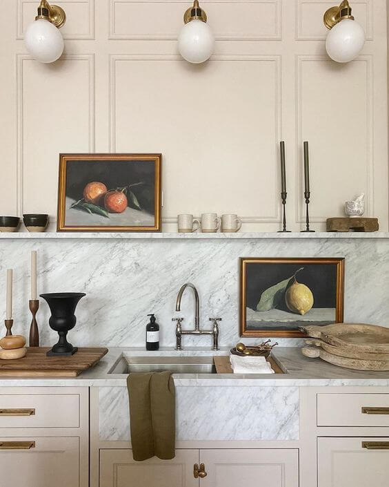 A close up of a kitchen bench. The benches are white and grey marble with beige cupboards underneath and brass handles. There is a sunken stainless steel sink with stainless steel hardware. An olive green tea towel hangs out of the sink, a chopping board is on the left with a black vase and some tapered candles on it and various boards sit on the right of the sink. There is a grey marble splash back with a white floating shelf above it. An oil painting depicting fruit sits on the shelf, with a matching piece depicting a lemon resting on the bench below. Some candles and kick knacks also sit on the shelf. The wall behind the shelf is a soft peach colour with three round hanging lights
