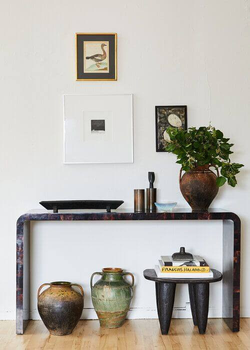 Photo by Nicole Franzen. Three photos are hanging on a white wall above a side table. They are arranged in different frames, one with a large white matt surrounding the image. A vase and tray sit on the desk with artistic potted vases sitting on the floor underneath.