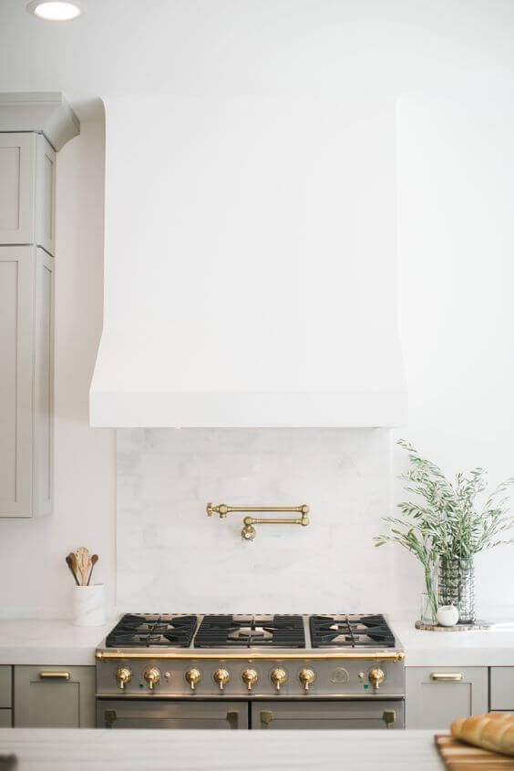 A close up of a stove and rangehood. The rangehood has been plastered white to blend in with the wall. The stove top is stainless steel with gold knobs and a gold valve is attached to the grey wall between the stove and rangehood. White benches can be seen either side with grey cupboards underneath, a plant sits on the right and a white vessel with wooden spoons in it sits on the left.