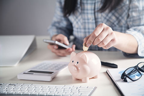 Business girl putting coin in a piggy ba