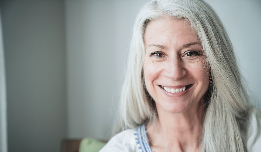 A white woman with long white hair smiling.