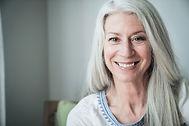 Smilende Eldre kvinne med grått hår