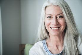 Glimlachende rijpe vrouw met grijze hare