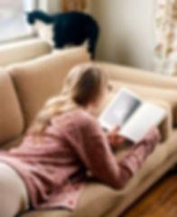 Девушка лежит на диване и читает книжку про бальные танцы