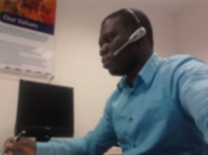 Man in and office with an ear piece on h