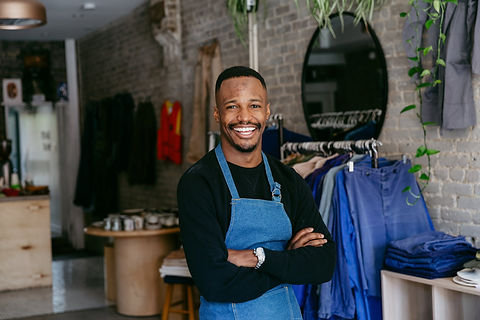 a-man-in-denim-apron-smiles-for-the-came