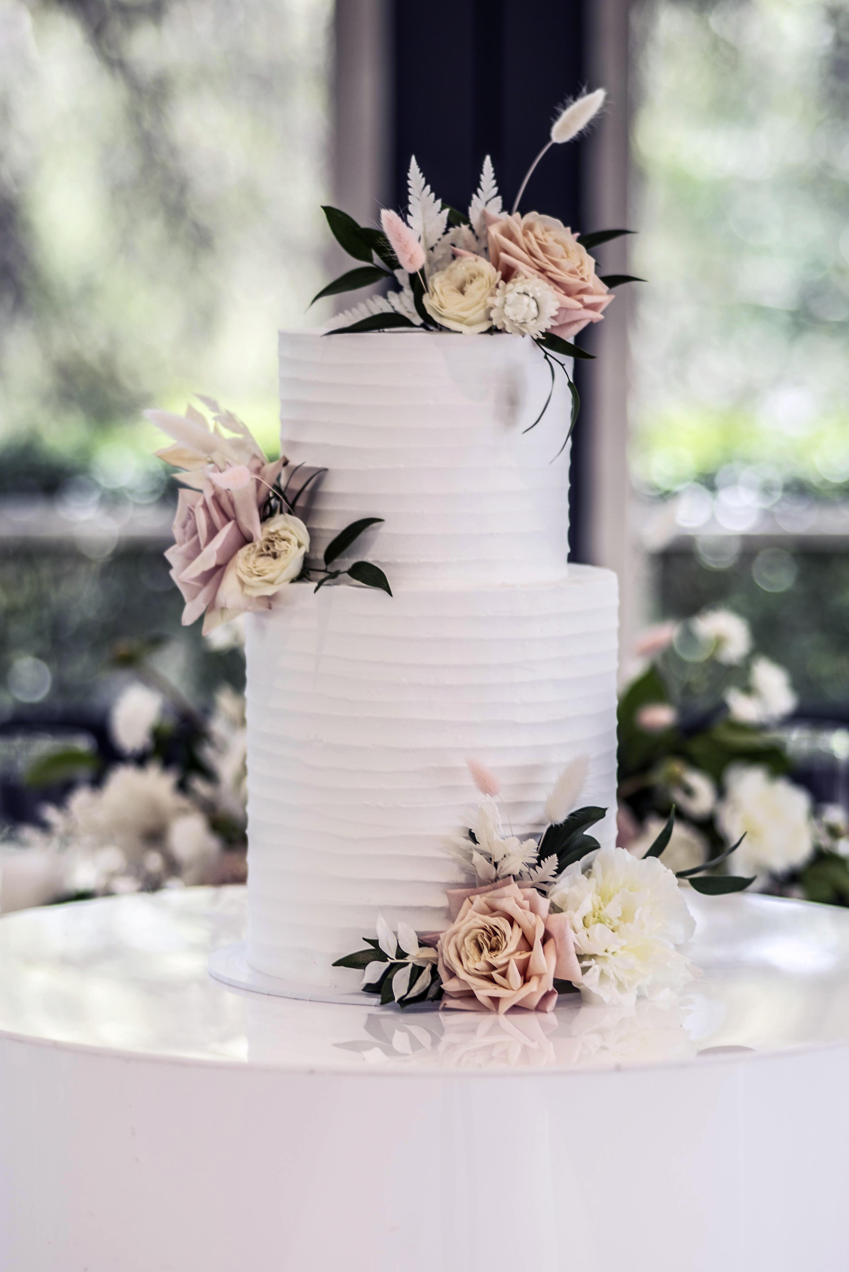 Blush pink and cream flowers on a white cake