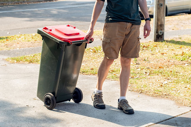 A man dragging the household wheelie red