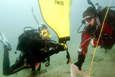 Scuba divers lifting an object with a lift bag in PADI Search and Recovery course.
