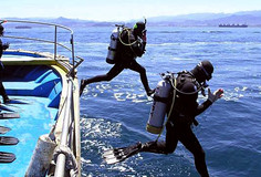 Scuba divers entering the water with giant stride entry.