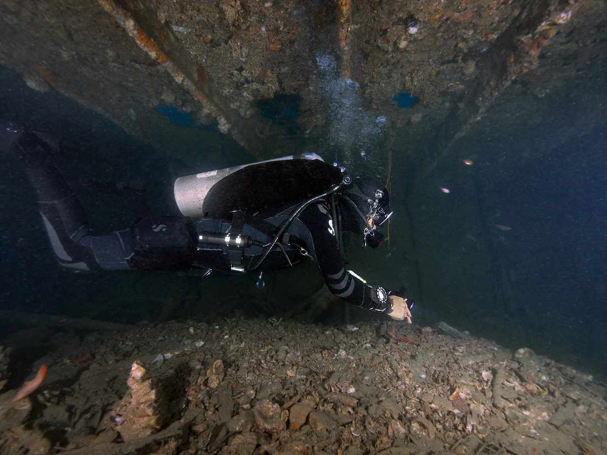 Wreck diver in a low corridor