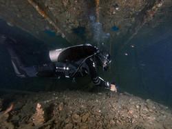 Wreck diver in a low corridor