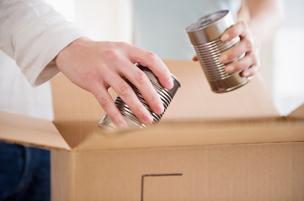 Food cans being placed in a carton