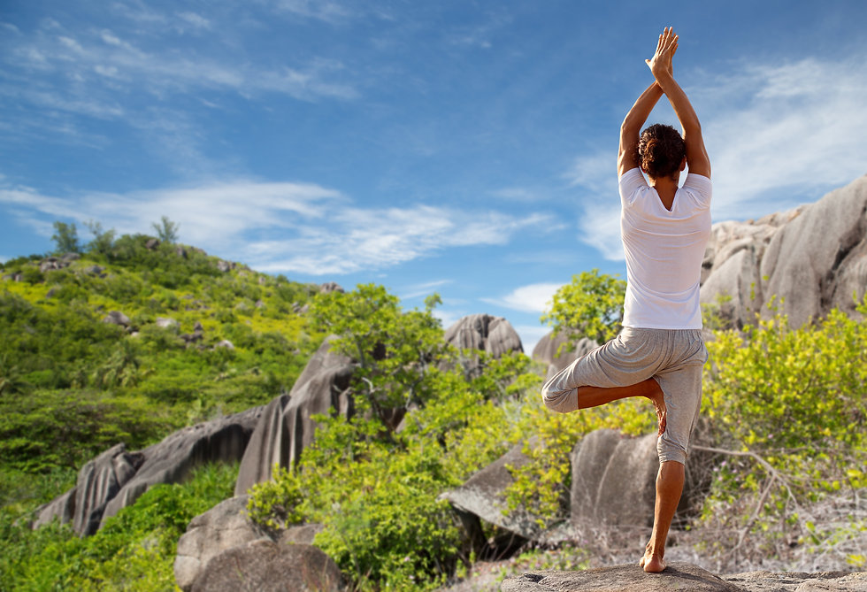 young-man-making-yoga-tree-pose-outdoors