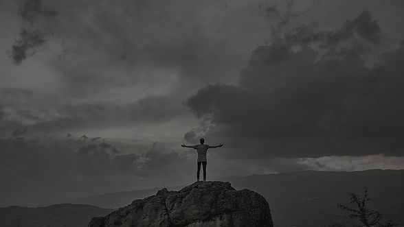 Person standing on mountain feeling successful and stress free