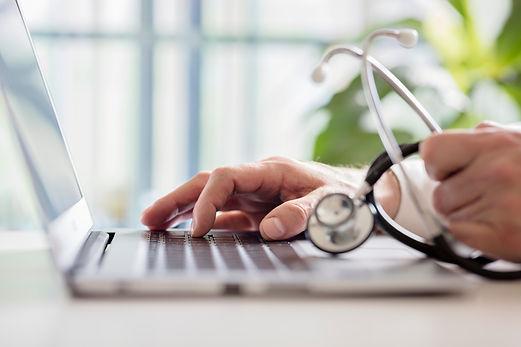 doctor-entering-patient-notes-on-laptop-