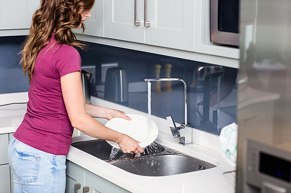 woman washing dishes, how to choose a new kitchen sink, choosing a new sink, buying a new kitchen sink, kitchen sink considerations, which sink is right for me, types of kitchen sinks