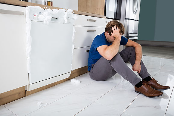 man with sudsy dishwasher, dishwasher leaks and malfunctions, common dishwasher problems, causes of dishwasher leaks, how to fix my dishwasher