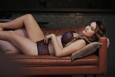 דוגמנית שוכבת על ספה עם חזייה ותחתונים