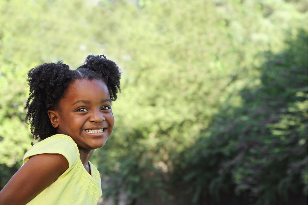 Image of a young girl outside, smiling for the camera.