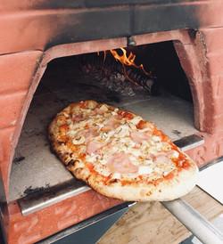 Metiendo Pizza en horno de leña