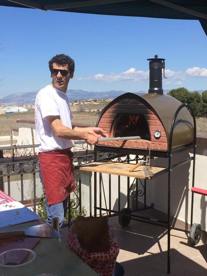 pizzaiolo en una pizza party con horno de leña