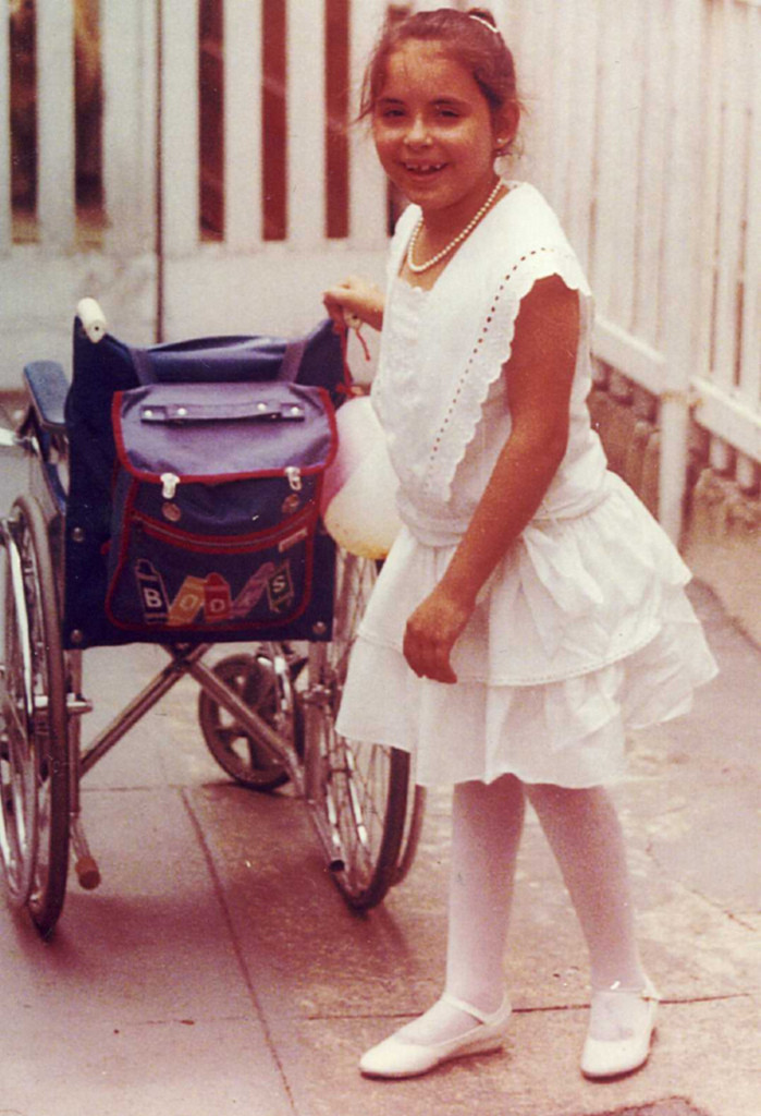 Photo of author Christinne Rudd as a child standing beside her wheelchair.