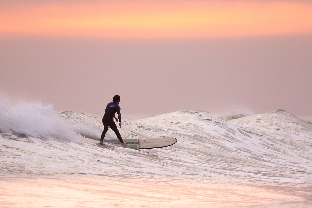 A silhouette of a surfer on a longboard riding one of the last, mellow waves of the day as the sun sets into a pastel orange, purple, and pink sky, and subtly reflects the same off the sea