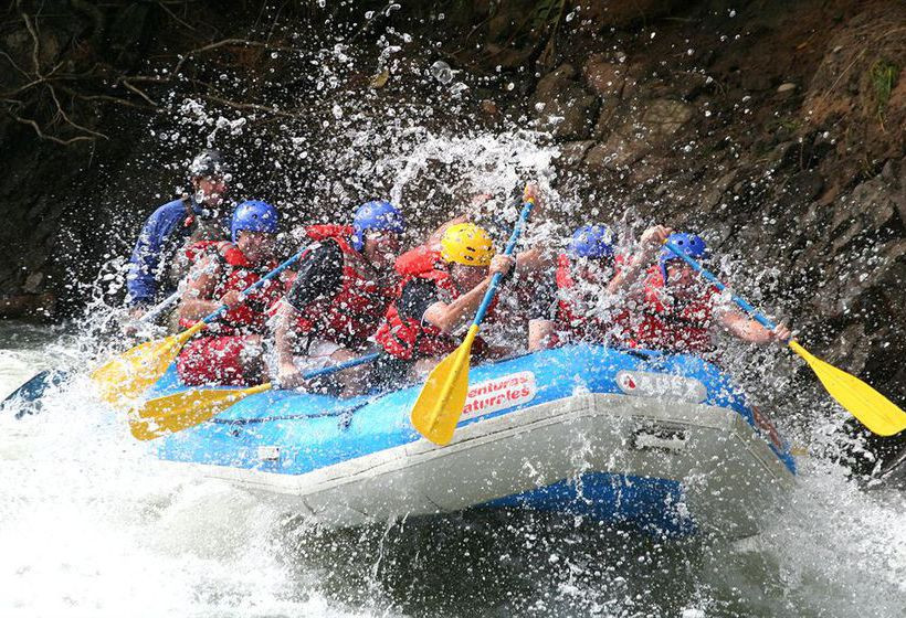 An exciting, close-up action shot of a bright, blue raft, full of helmet and life jacket wearing thrillseekers, charging through the white water rapids, as spray from the river erupts around the vessel