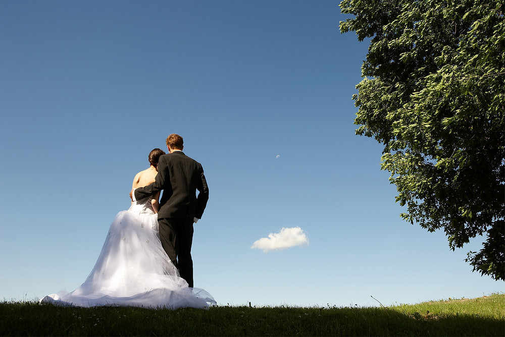 Newly weds embrace under blue skies