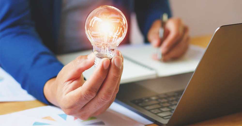 Businessman holding a light bulb in front of a laptop