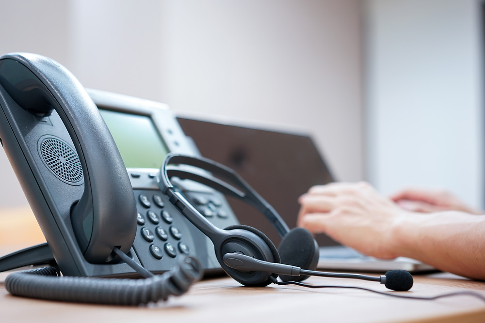 Telephone with headphones at support helpdesk