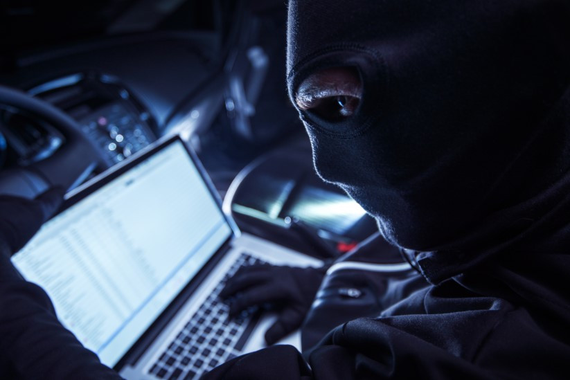 Hacker on the laptop stealing sensitive information