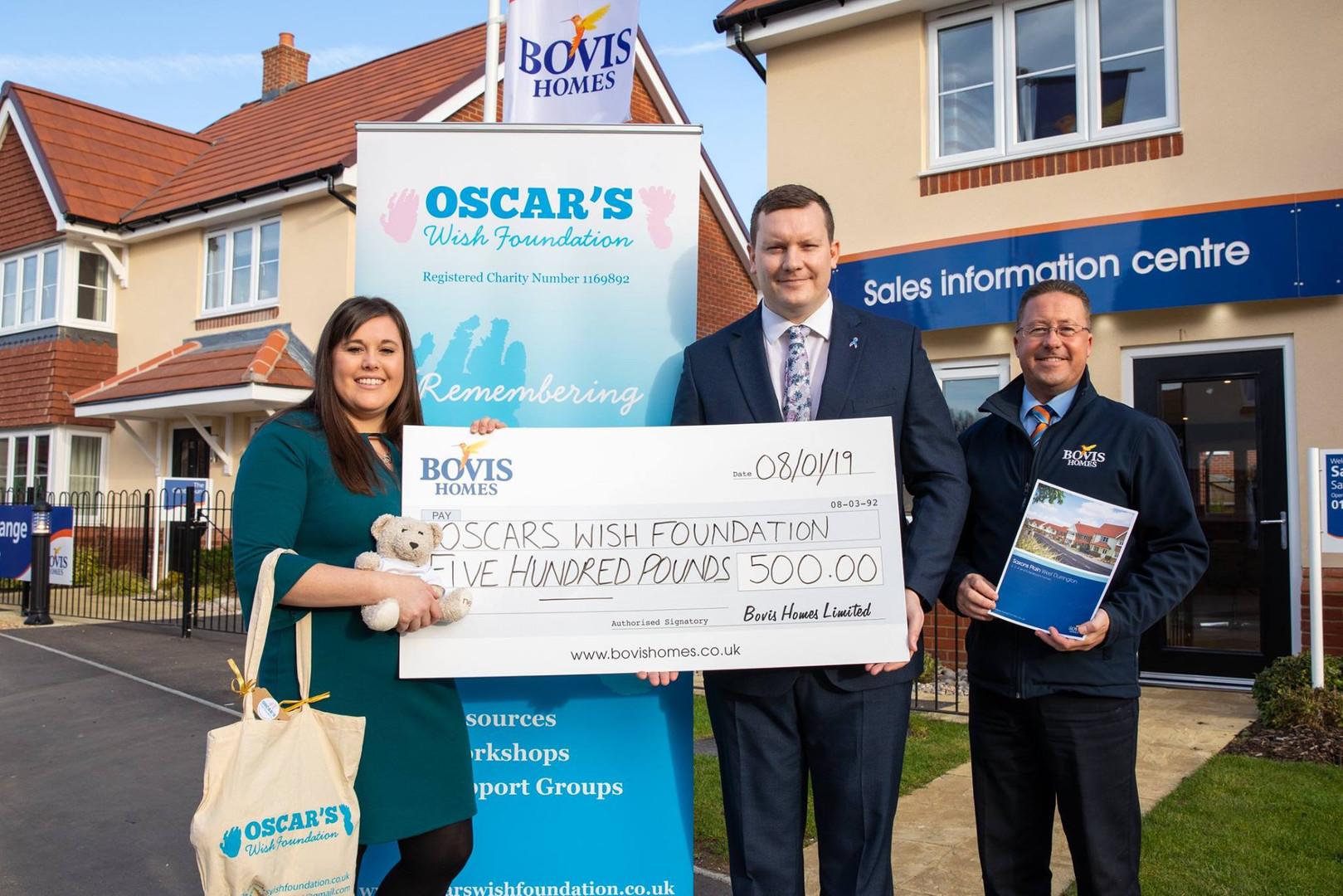 Gemma Kybert receiving a cheque from Bovis Homes