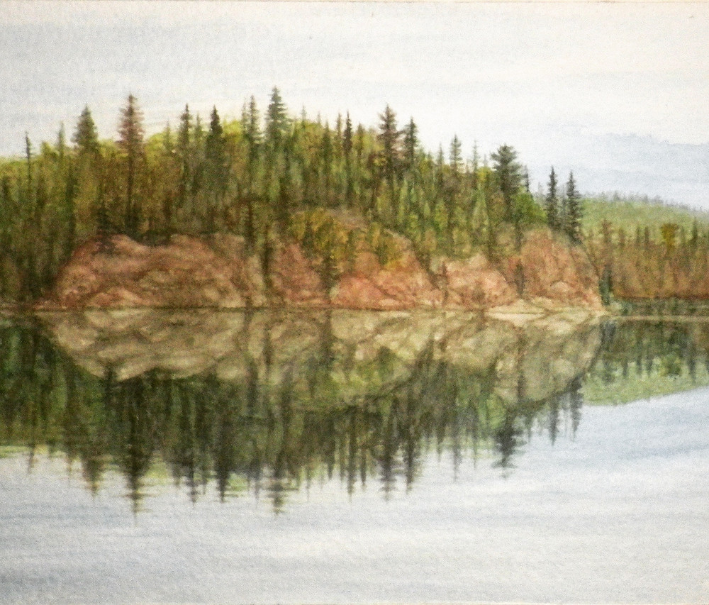 The calm waters of Old Woman Lake reflect a rocky, treed shoreline on a cloudy day