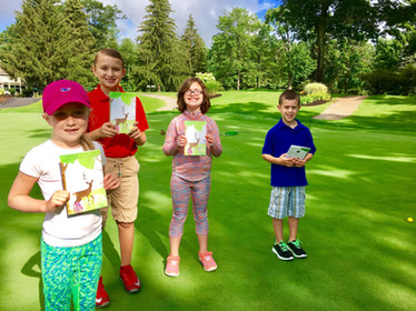 Junior golfers enjoying coloring books during summer camp.