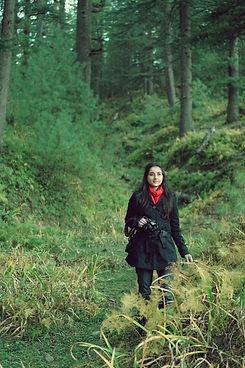 Kriti Bajaj standing with a camera in green Himalayan woods. © Sahil Bajaj