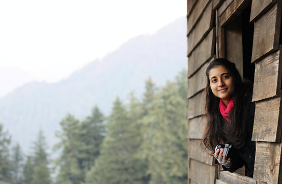 Kriti Bajaj looking out the window of a wooden hut with Himalayas in the background. © Sahil Bajaj