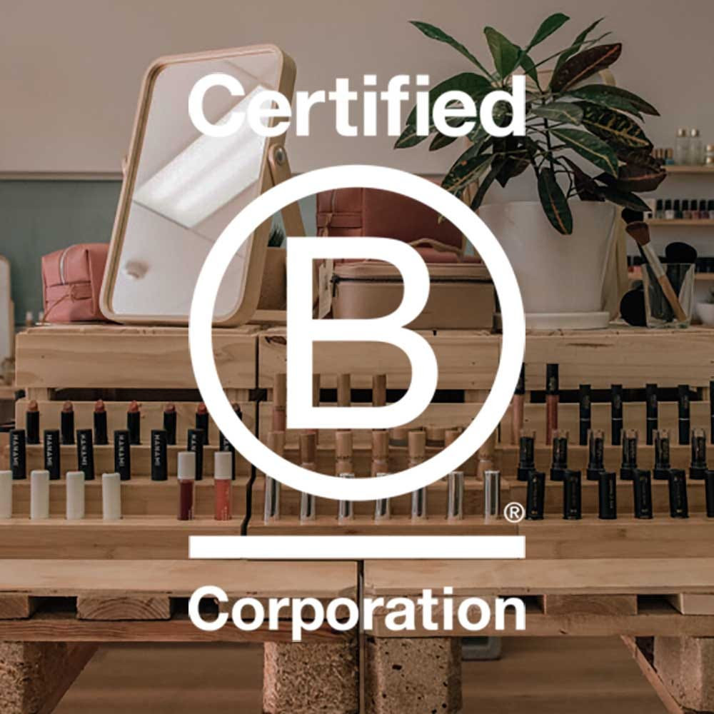 Certified B Corporation logo layered over a wooden display of makeup. With a wooden mirror, makeup cases, plant, and makeup brushes on top of the shelf