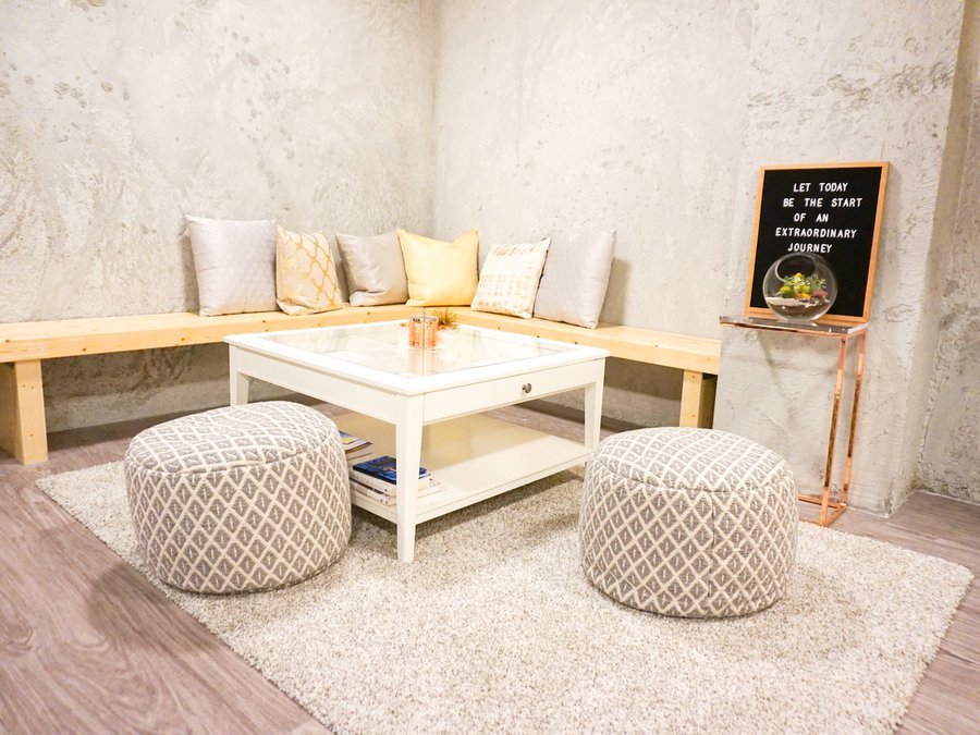 "loby of Hive Fit Co - slate cement walls in a well lit room with big wooden wrap-around bench, cushions and coffee table. A letter sign that reads ""Let Today Be The Start of An Extraordinary Journey"" with a plant terrarium sitting underneath on a brass side table."