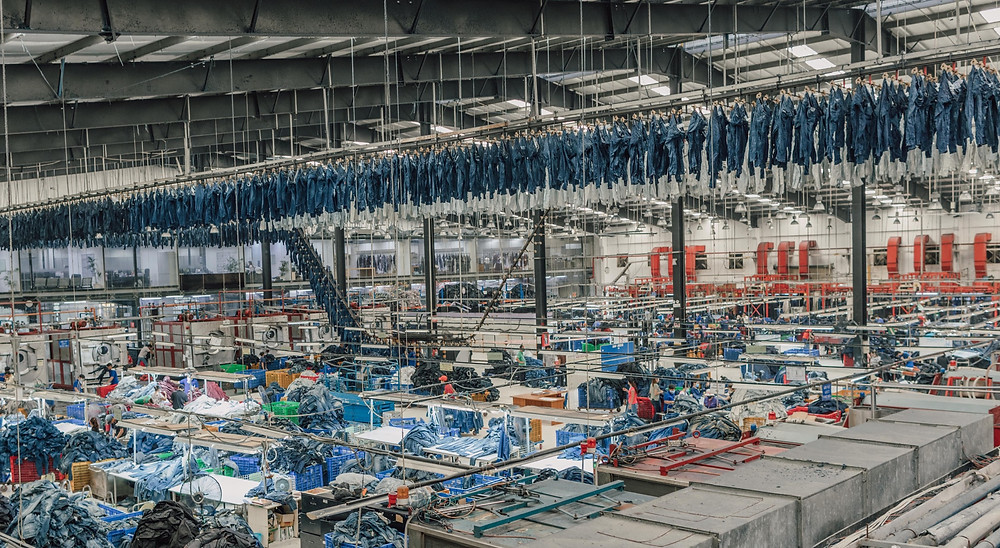 denim factory with blue jeans airing to dry above a warehouse full of industrial sewing machines and piles of denim fabric on tables