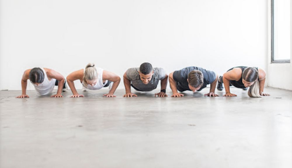 5 people in low plank pushup position in a white brightly lit room
