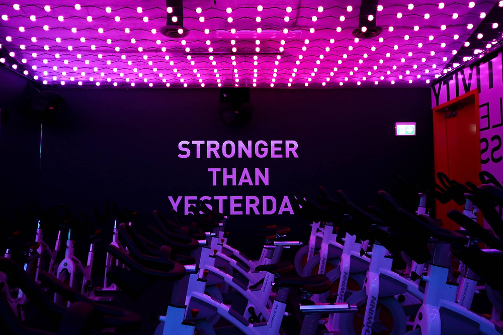 "Spin studio in YEG Cycle with stationary bikes and. Ceiling is lined with small lights and the feature wall has large block letters painted on it that read ""Stronger Than Yesterday"""