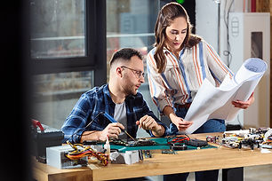 woman-and-man-engineers-looking-at-hardw