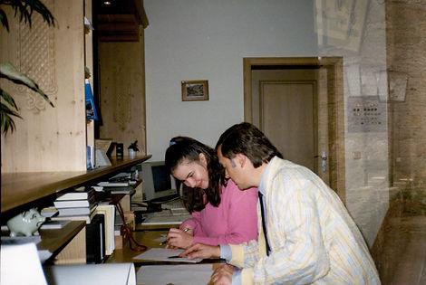 Kurverwaltungsleiter von Kreuth Rudi Wolf erklärt Christine einige Aufgaben auf Papier in der Kurverwaltung Kreuth