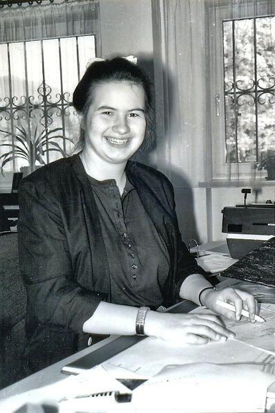 Christine lächelte, sitzt am Schreibtisch mit Papierunterlagen in Rathaus Kreuth