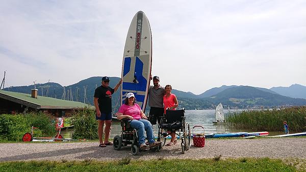 Christine am Ufer mit dem SUP und der Gruppe im Hintergrund
