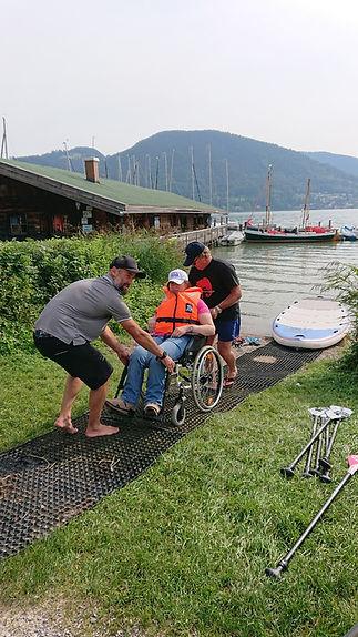 Der Rollstuhl von Christine wird zum SUP geschoben