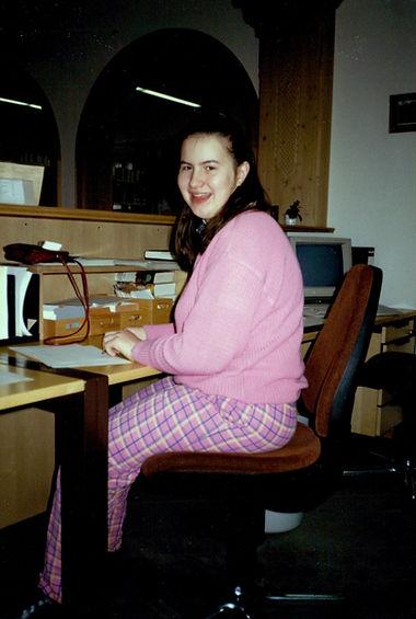 Christine lächelte, sitzt am Schreibtisch mit Papierunterlagen in der Kurverwaltung Kreuth